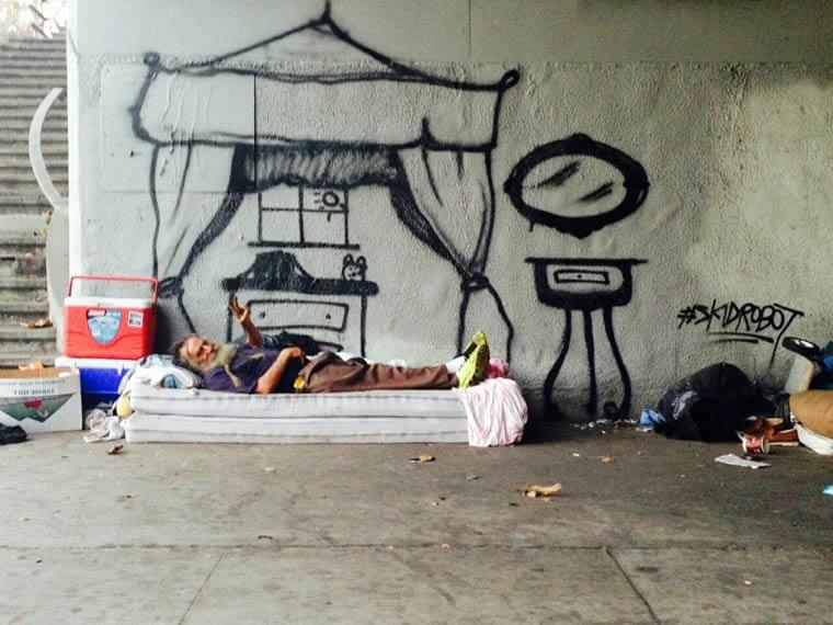 A street artist paints the dreams of homeless